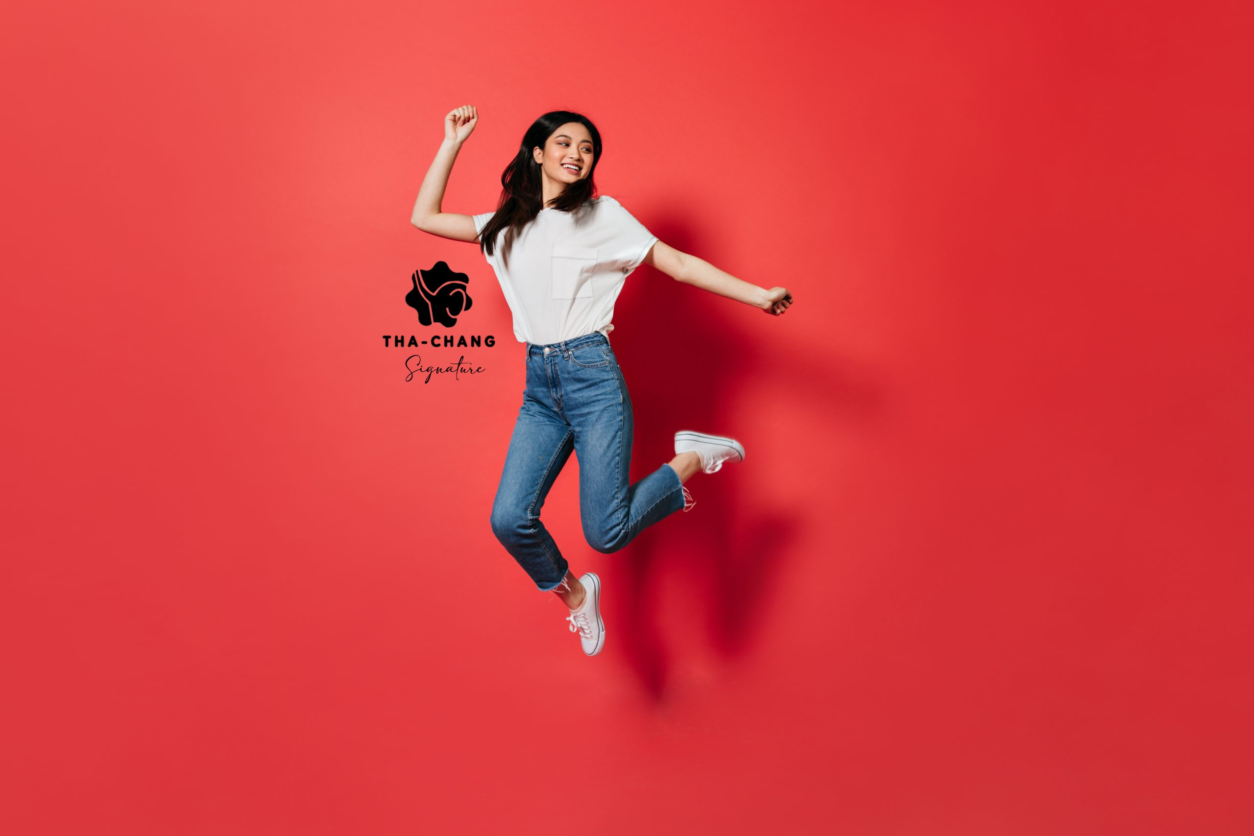mischievous woman white t shirt jeans jumping red wall1 scaled